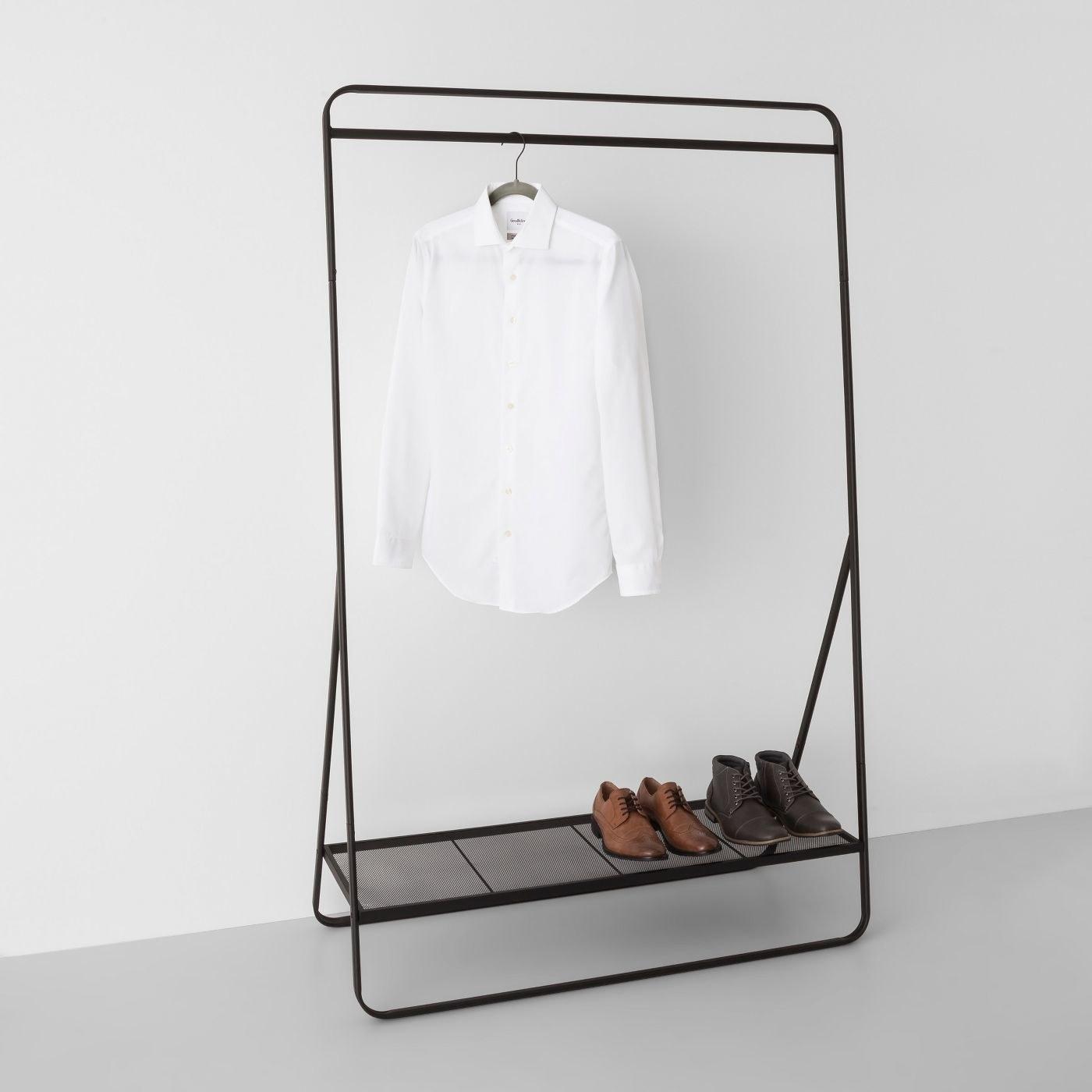 a black standalone garment rack with a shoe shelf