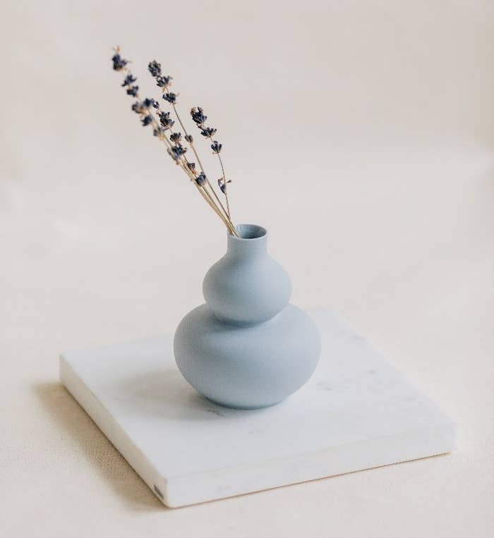 Small double gourd mini vase in blue with a couple of strands of dried flowers in it