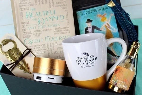 A box filled with a book, a coffee mug, and other bookish items