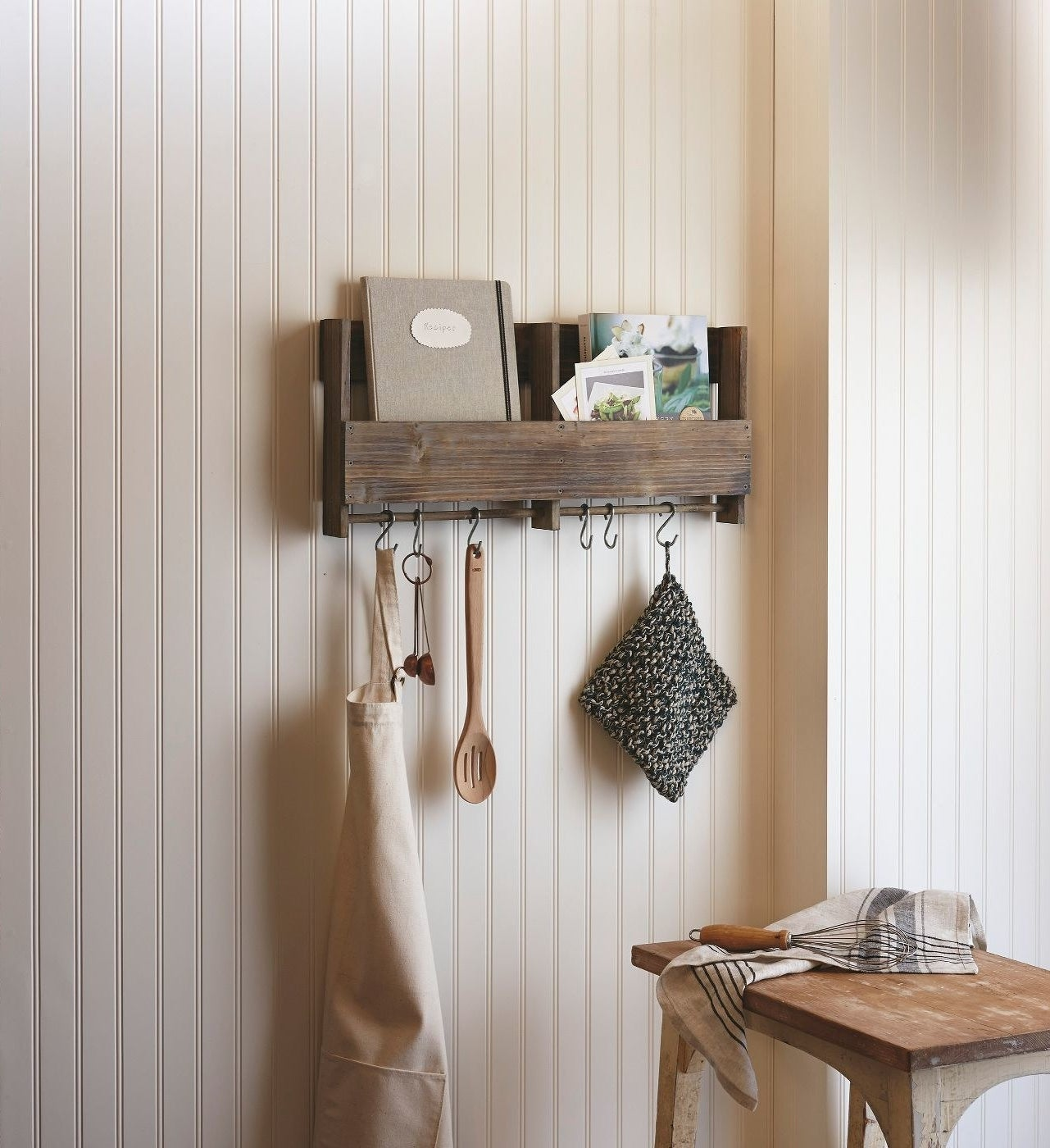 A wooden shelf with two sections in brown and a bar across the bottom with six s-hooks with random kitchen things hung on them