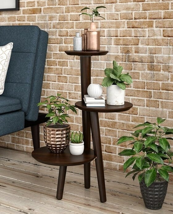 A dark brown wood plant stand with three shelves