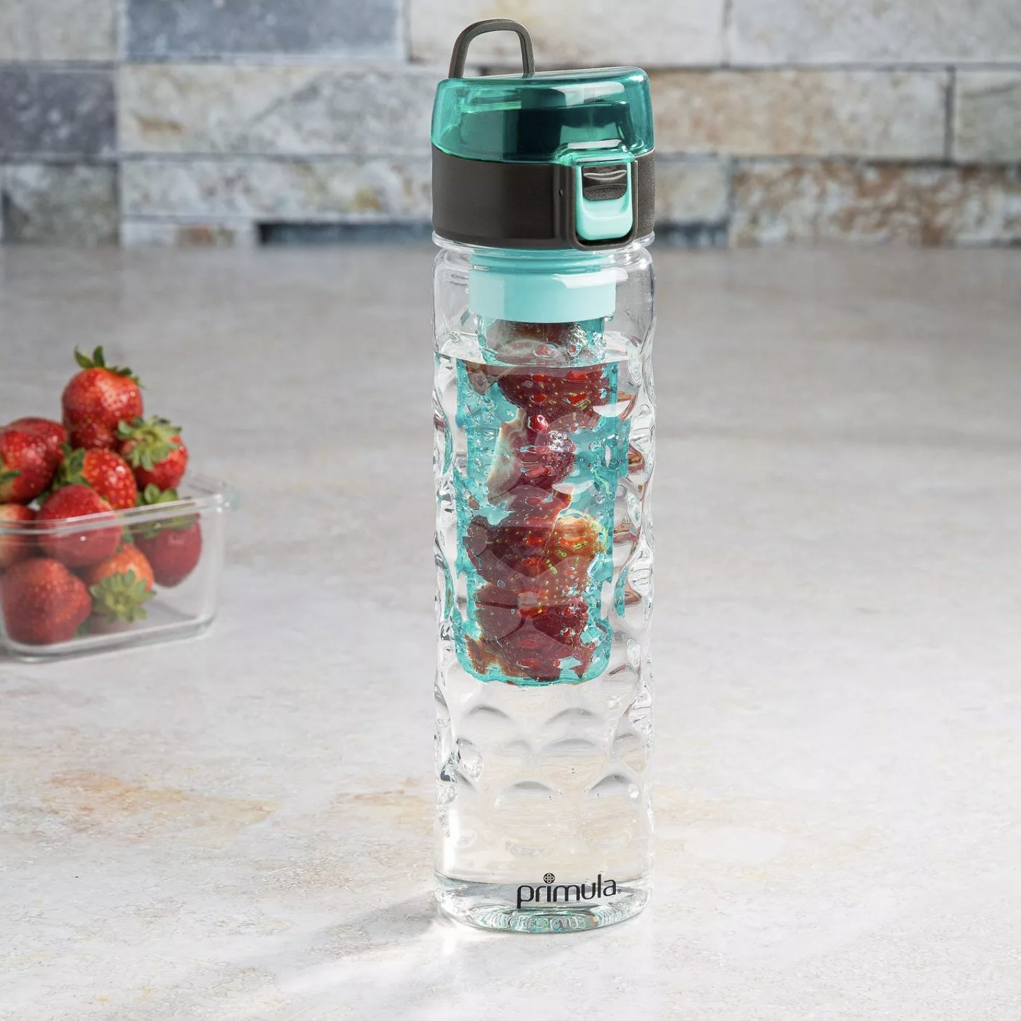 A transparent water bottle with an infuser full of fruit on the inside