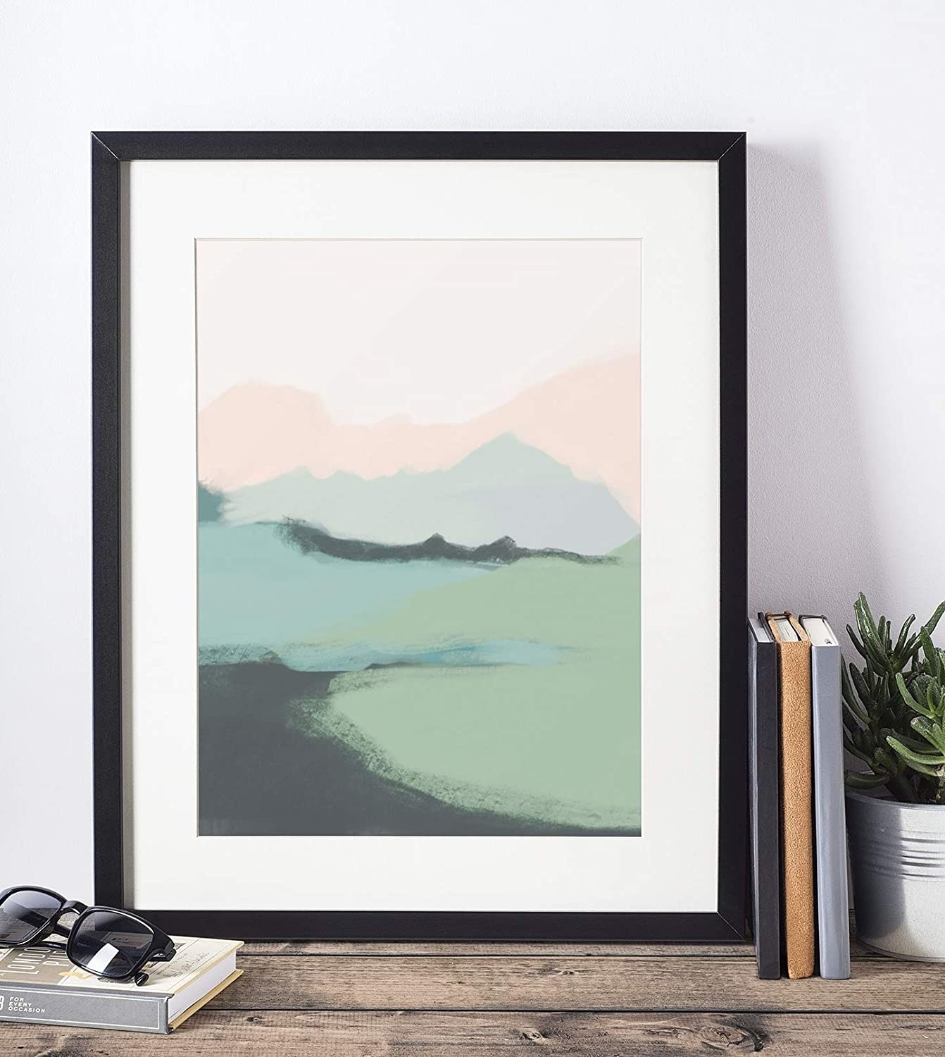 The art print with an abstract feel that looks like a light pink sky, and pink and green mountains and green meadow at the bottom