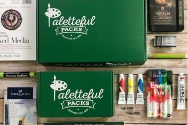 The exterior of the Paletteful Packs boxes along with supplies like paint  and a mixed media book