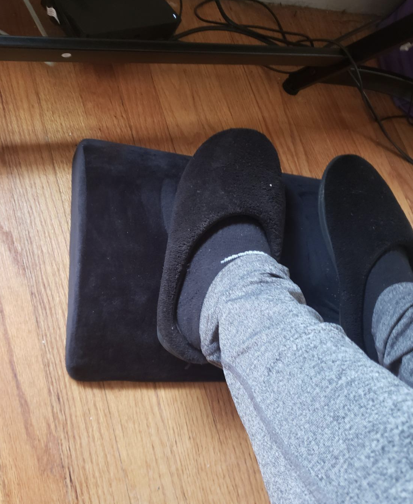 A reviewer image of a person's feet on the black foot rest pad under a desk