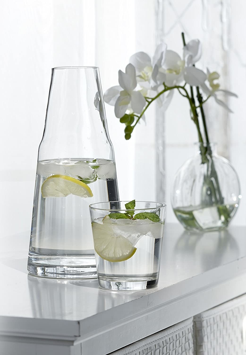 A glass water pitcher and small glass sitting next to it, both filled with water, ice, lemon slice, and mint