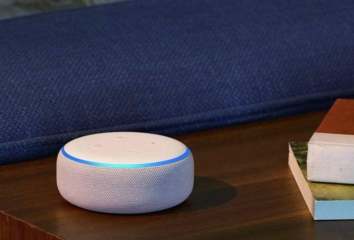 A white circular Amazon Echo dot on a table