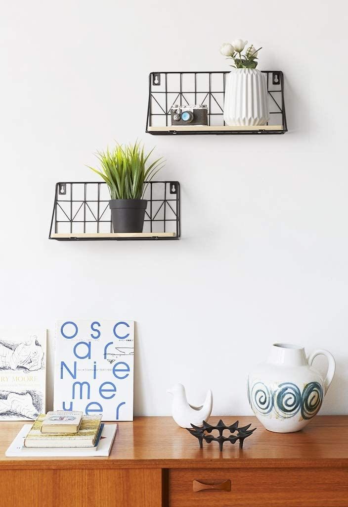 Two floating shelves on a wall with a wood base and a black wire back with assorted plants and trinkets on them