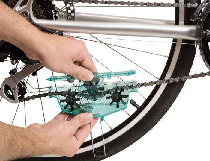 A person clipping the bike chain doodad to their bike chain