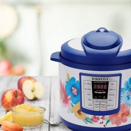 A white Insta pot with flowers on it and a blue lid and base