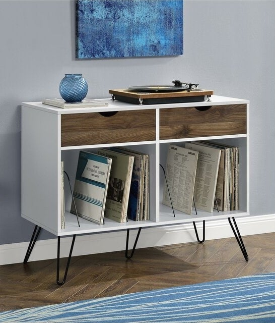 A white cabinet with black metal legs and brown wooden drawers that holds records