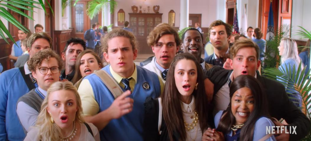 Students gather around a bulletin board in their high school hallway.