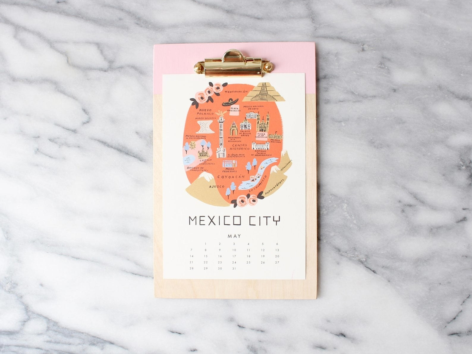 A small clipboard made of wood with a block of pink at the top and a gold clip with a calendar page on it