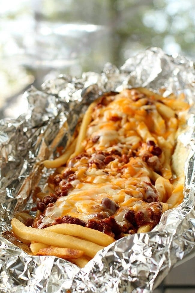 A tin foil packet full of french fries topped with beef chili and melted cheese.