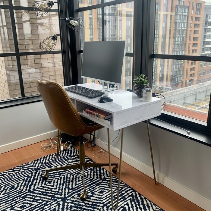 A reviewer's photo of a white marble color desk with two open drawers
