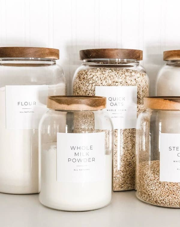 "Assorted glass jars with square white labels ion the front saying what's inside the jar including ""Whole Milk Powder"" and ""Flour"""