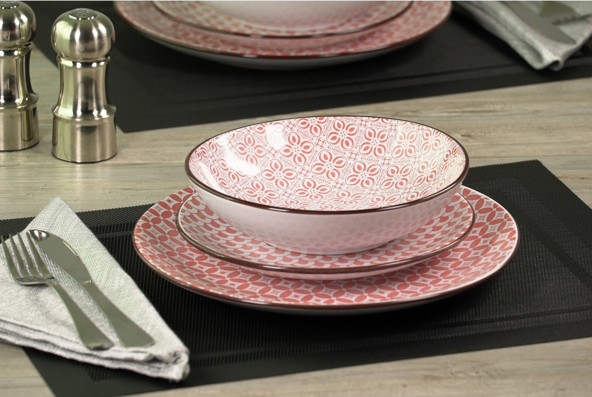 A ping and white patterned dish set of a plate, a smaller plate, and a bowl
