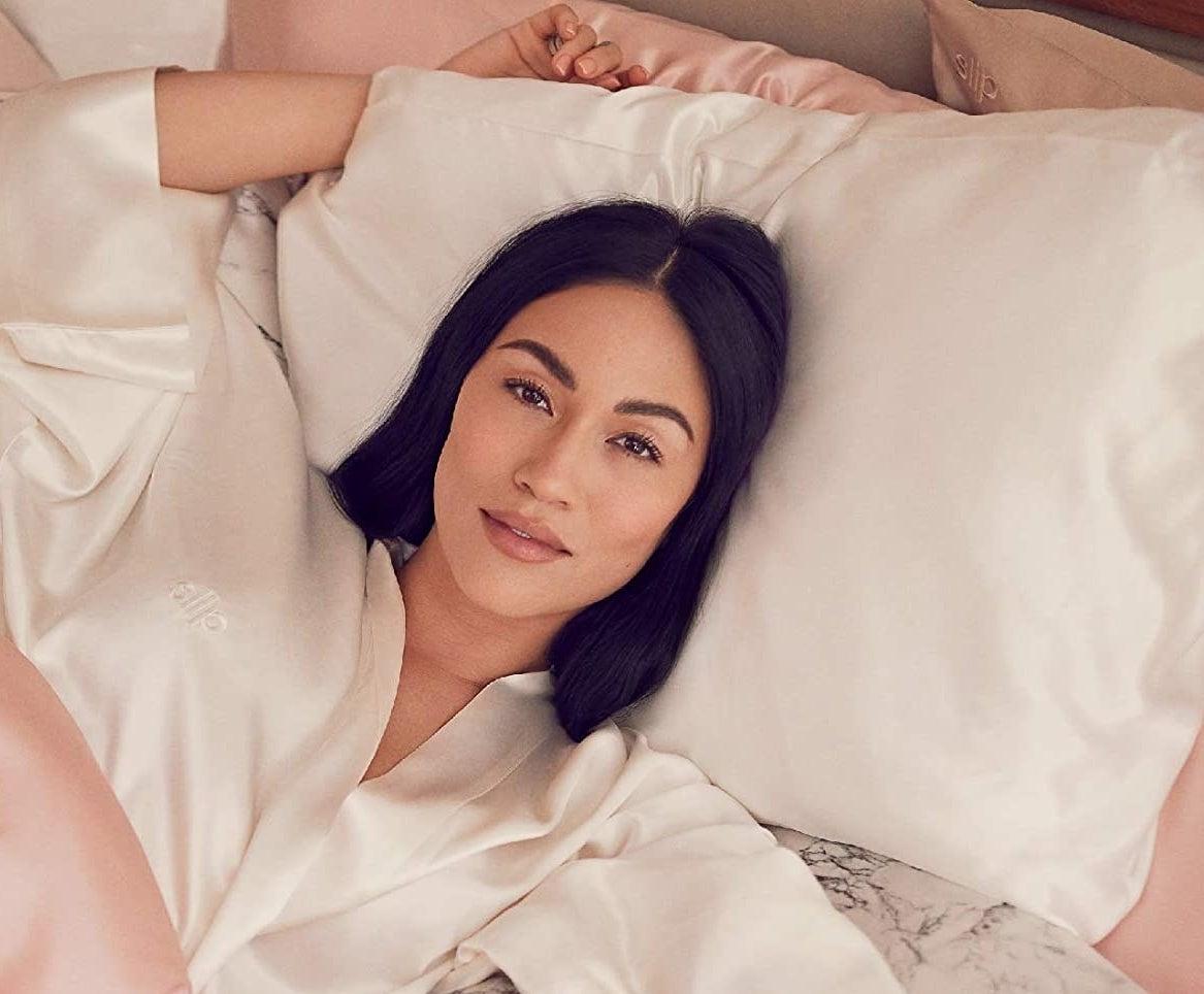 model laying on white silk pillowcase