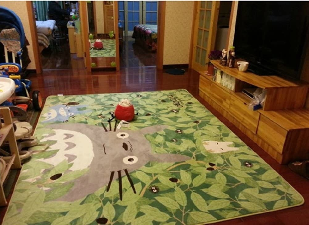 A green rug with Totoro on it spread out in a room