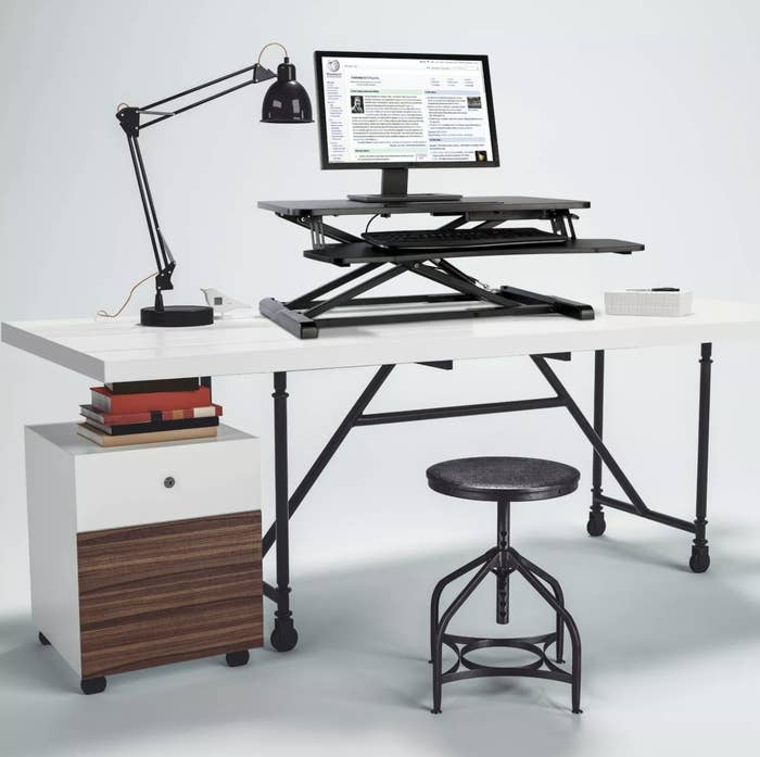 A black standing desk with a keyboard and monitor atop it