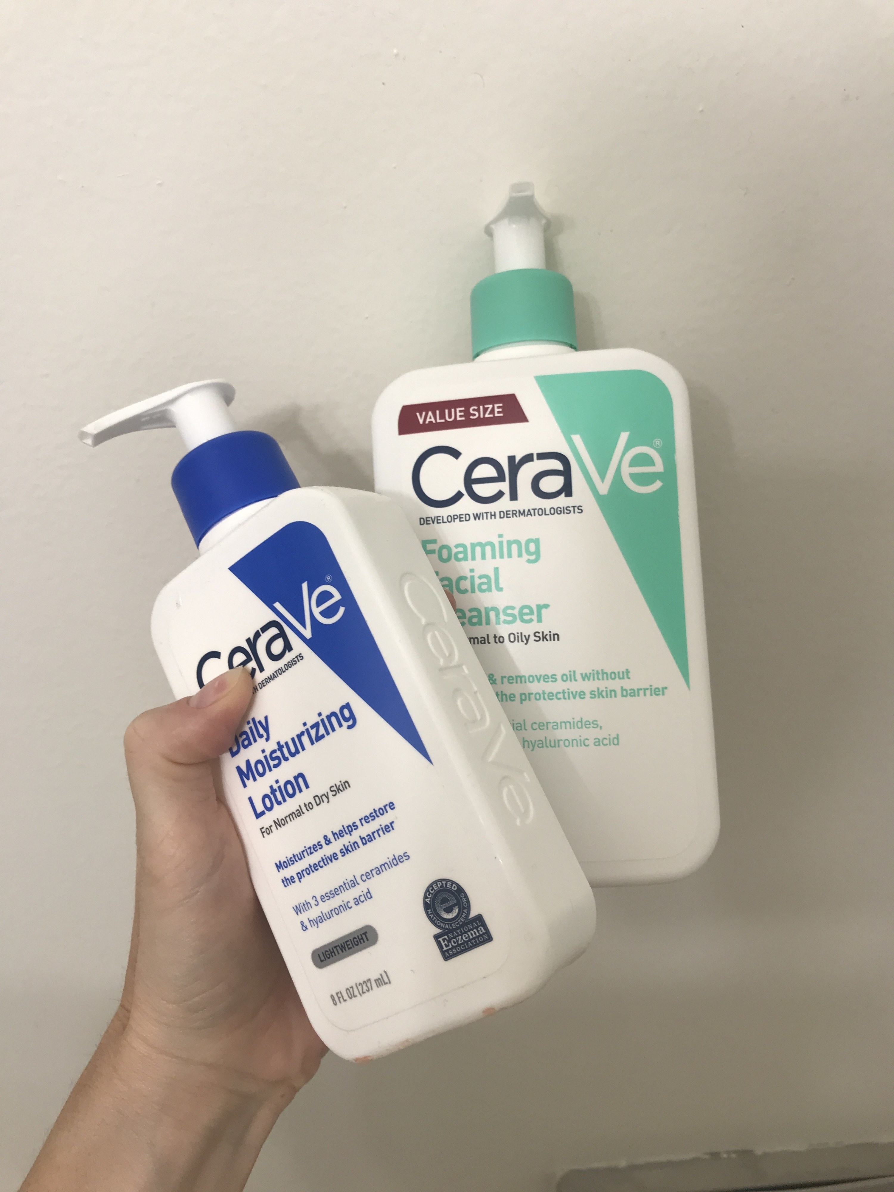 Hand holding Cera Ve products