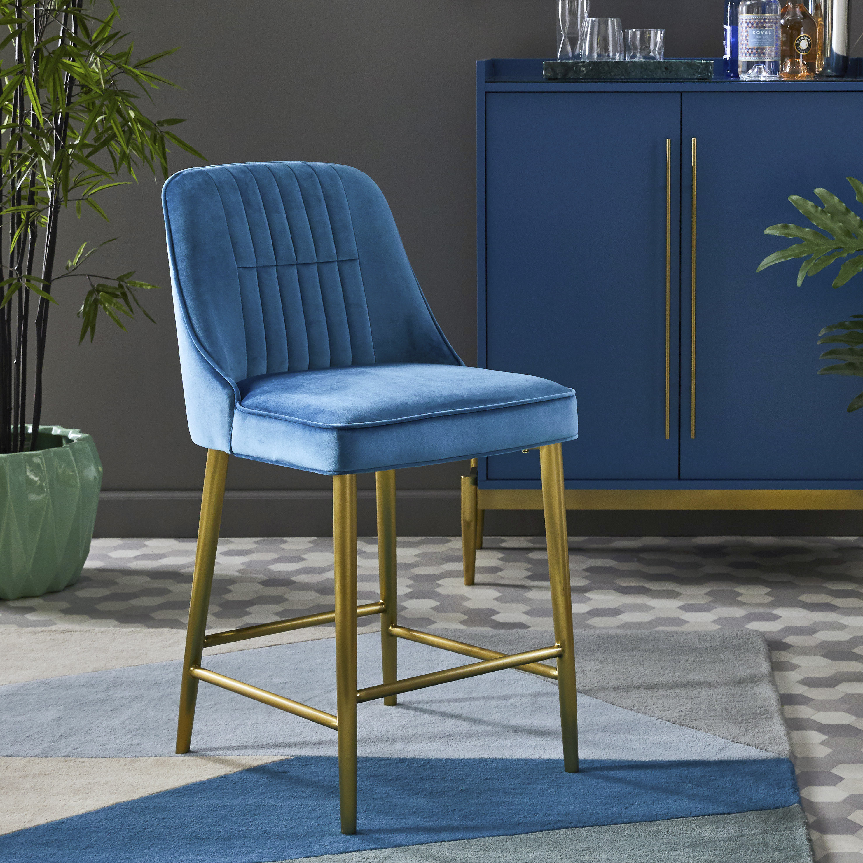A blue velvet bar stool with gold legs