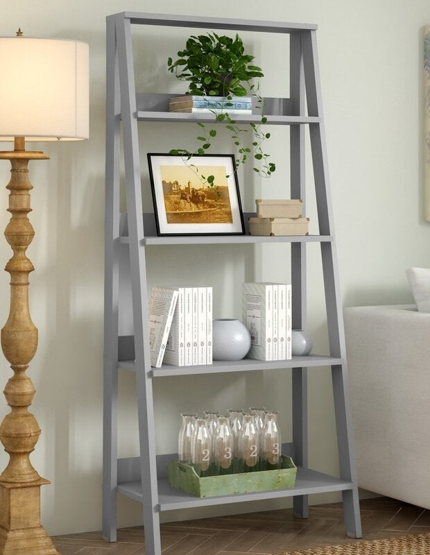 A light gray ladder bookcase with four shelves decreasing in size from bottom to top