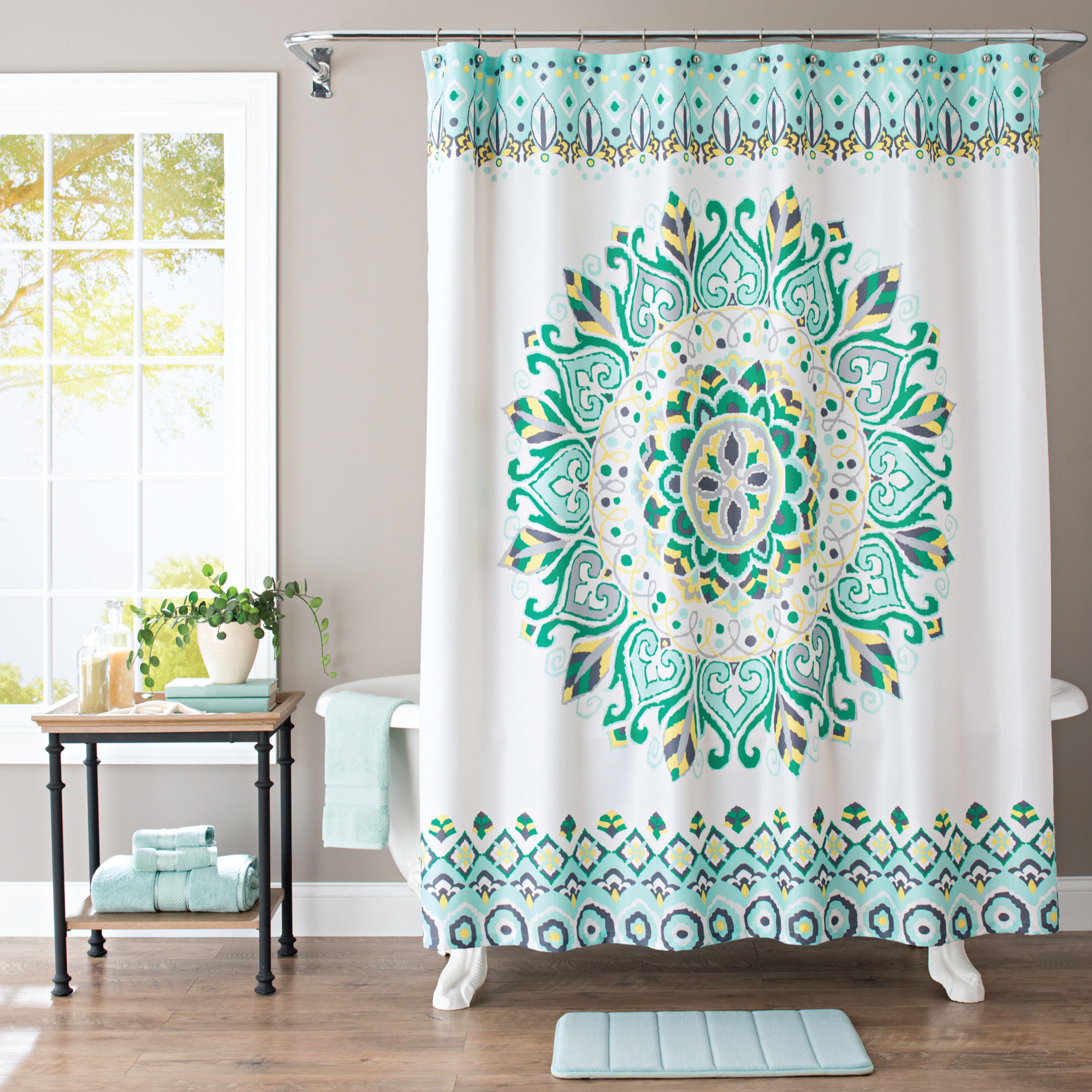 A white shower curtain with green, yellow, and gray medallion print