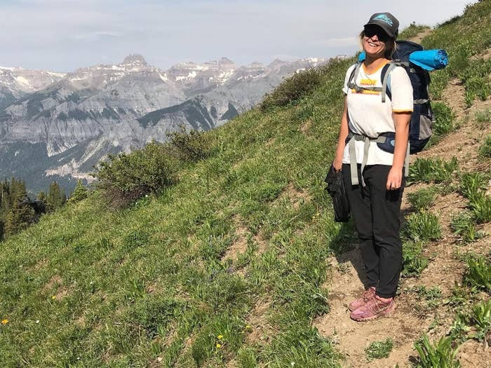 a woman standing on a hiking trail in the mountains, wearing a backpack with camping gear, smiling at the camera