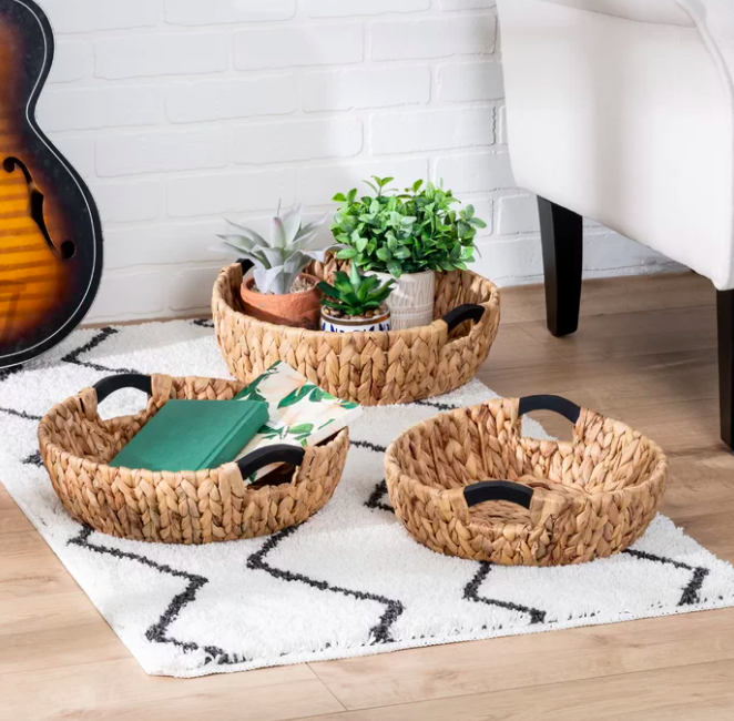 Three brown woven baskets filled with plants and notebooks on a white and black rug.
