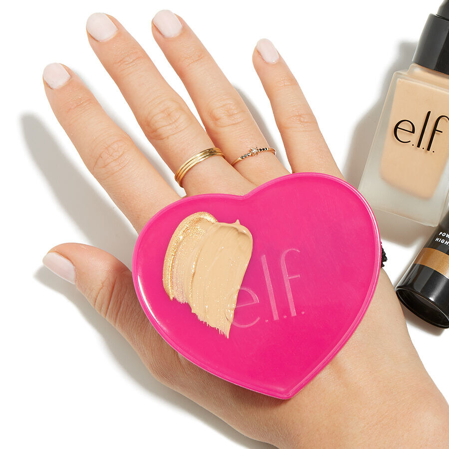 The pink heart-shaped plastic palette fastened to the back of a hand with a strap, with a swipe of foundation on it