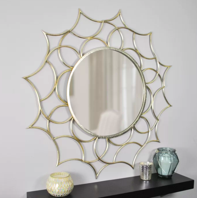 A silver sunburst mirror with a gold foil finish above a black floating shelf