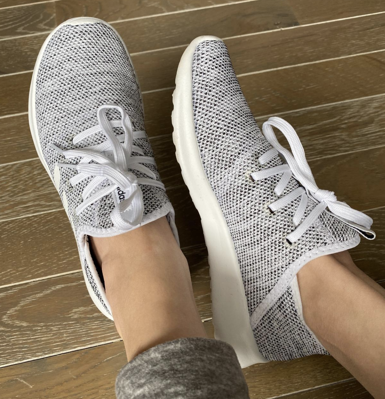 reviewer wearing white and gray lace-up sneakers