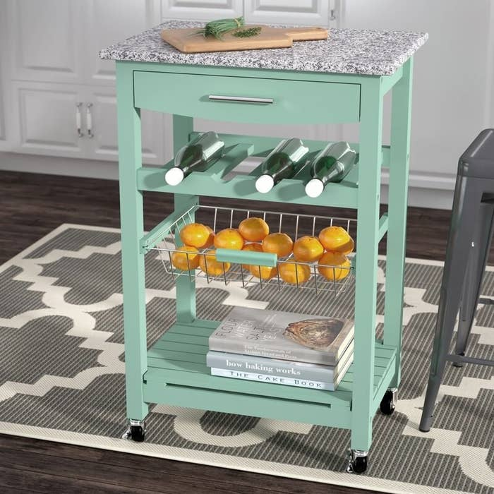 A seafoam green kitchen cart with a shelf, bottle rack, metal container, drawer, and a gray granite top
