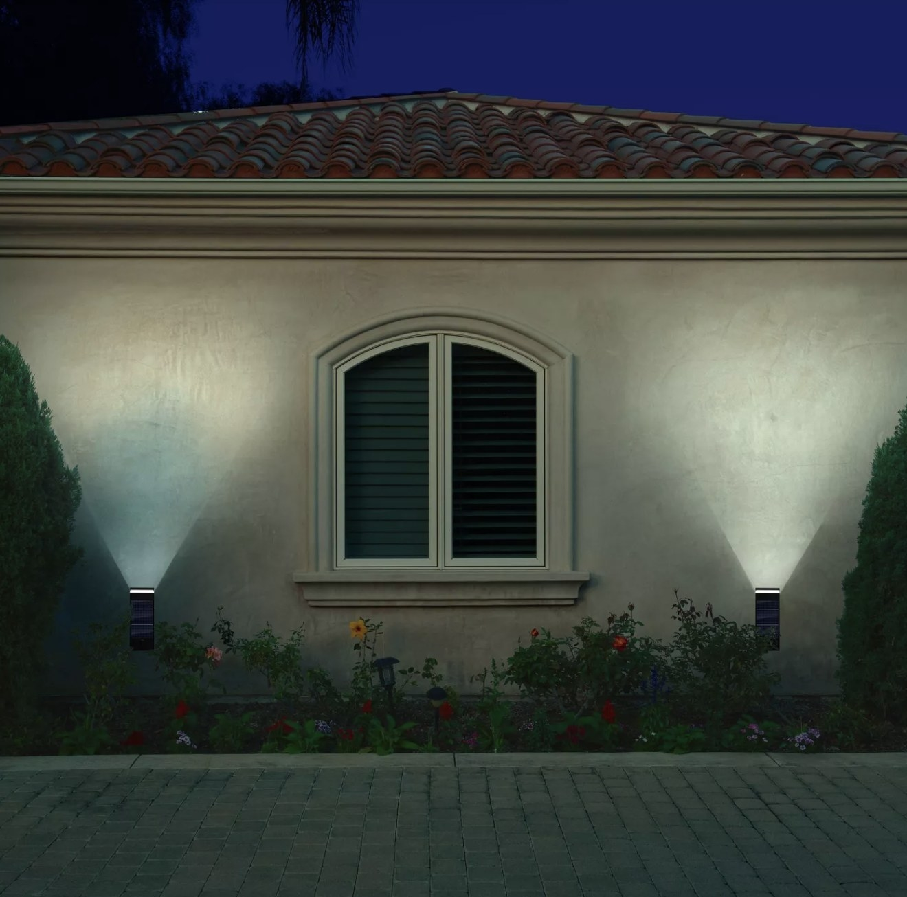 Two solar lights attached to the outside wall of a home illuminating the evening