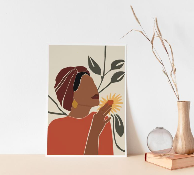 A colorful print with a Black woman holding a yellow sunflower on top of a table