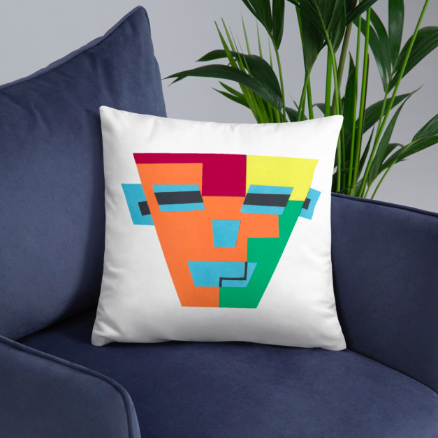 An accent pillow with a colorful-printed face on a dark blue arm chair