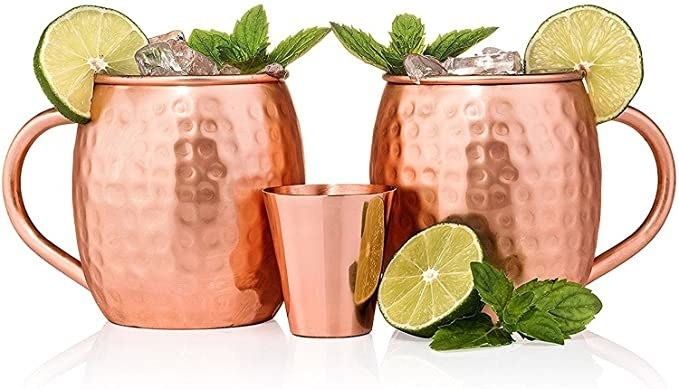 Two copper mugs are filled with liquid topped with ice mint and lime wedges with a copper shot glass