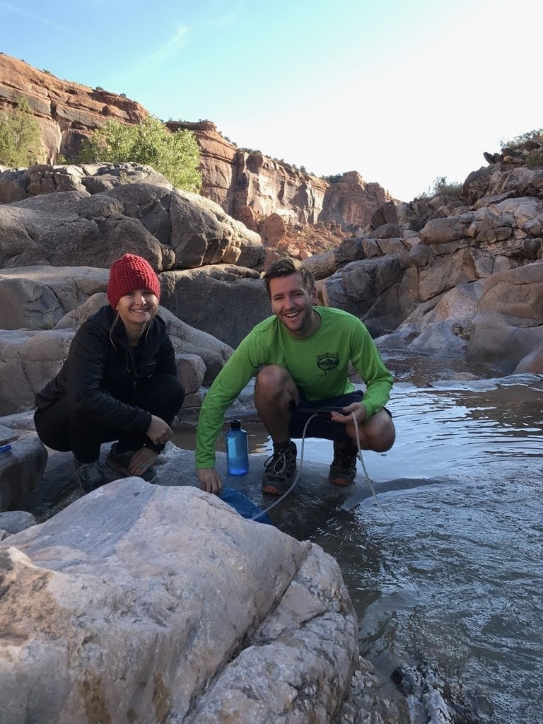 a couple filling up their water bottles from a flowing stream surrounded by rocky terrain