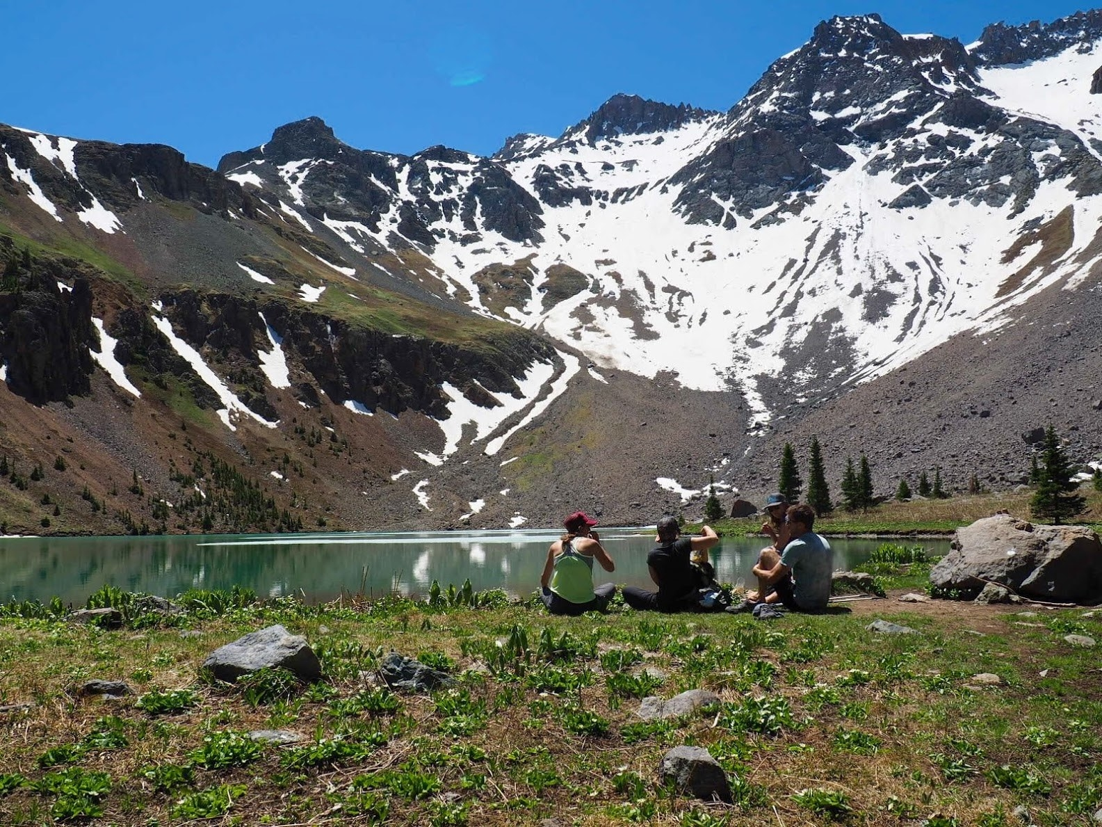 group of people sitting by a lake with a stunning snow-capped mountain in the background