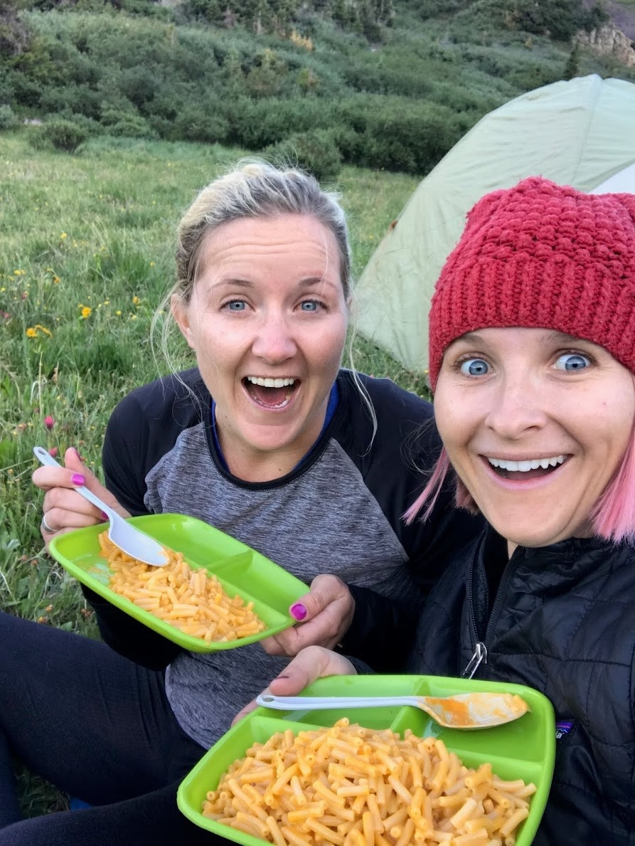 two women sitting on the grass eating packaged mac and cheese off plastic plates, smiling and taking a selfie