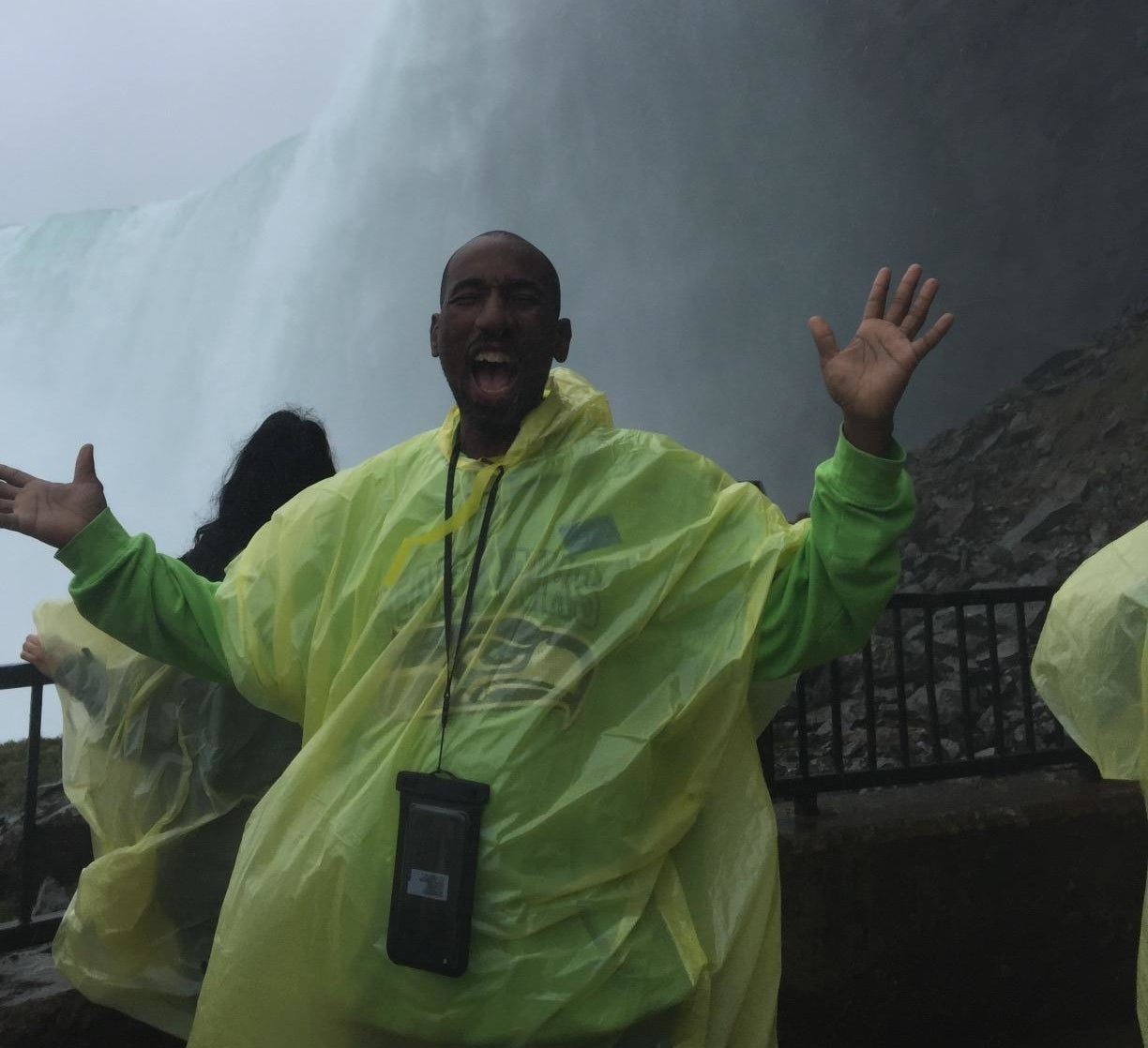 reviewer in poncho excitedly poses in front of niagara falls with phone in pouch around neck