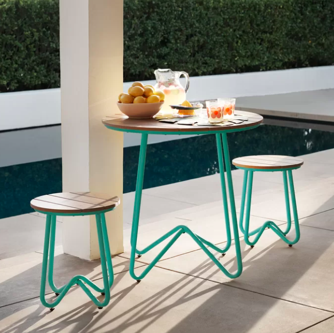 A turquoise table and stool set with drinks and fruit on a white patio