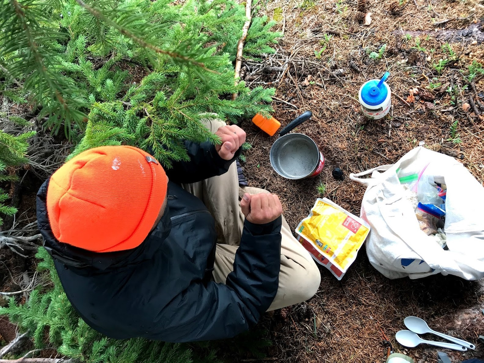 bird's eye view of a person sitting outside on the ground preparing to cook dinner on a small camping stove