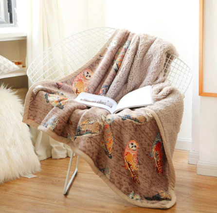 A brown throw blanket printed with owls on a wired chair