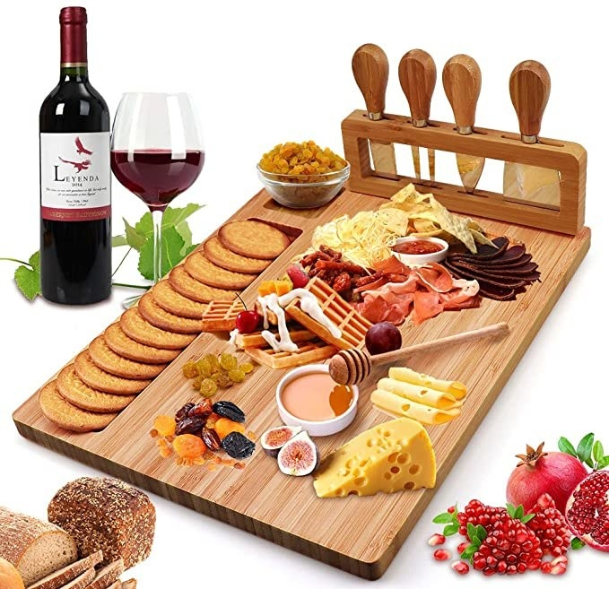 A cheese board with cheese, meat, crackers, dips and fruit on it