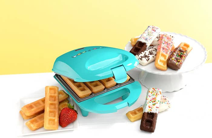 A waffle stick maker with waffle sticks on a plate some of which have been dipped in chocolate and have sprinkles