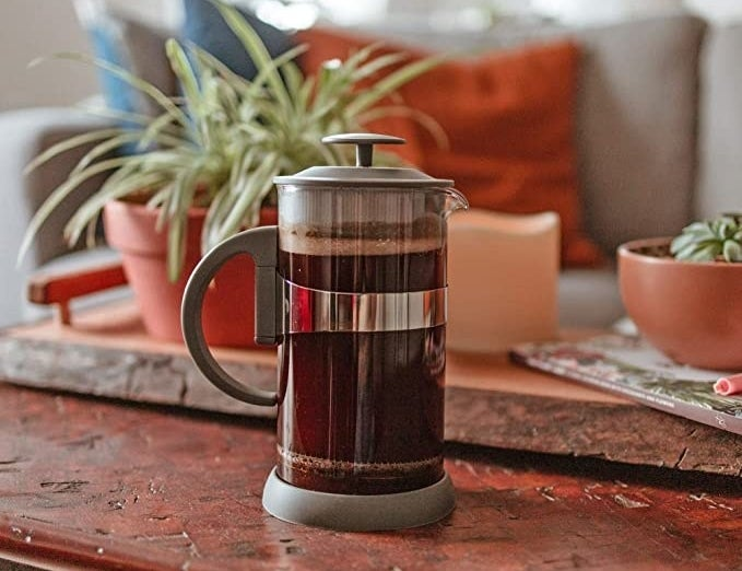 A french press filled with coffee on a table