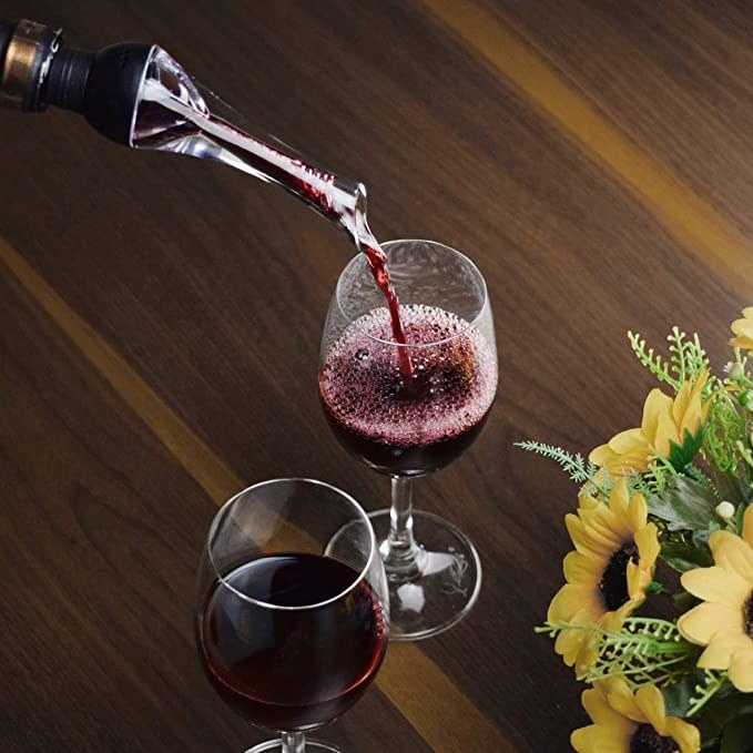 Red wine is poured into a glass using an aerator