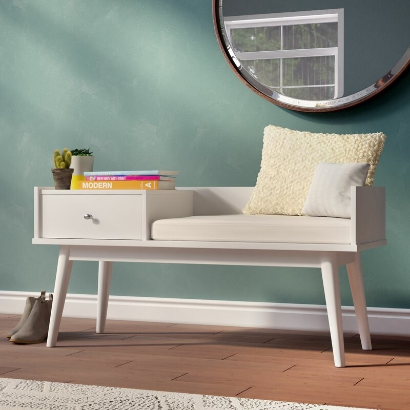 A cream-colored bench with one large drawer next to a seating area